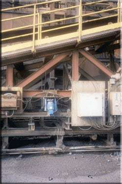 Thruster Rail Gripper, compact version, sill beam mounted, complete with hand release and release indicating limit switch.   Mounted on a tripper ore pellet conveyor at a steel plant.  The Rail Gripper maintains position while the ore pellets are transported on the conveyor.  The rail gripper also provides safety in the event of high winds.
